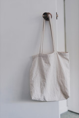 shopping and daily life, plain white canvas tote bag handging on door knob in front of wardrobe doors with minimalist look