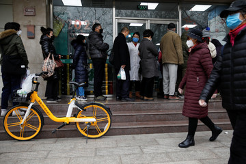 People queue outside a pharmacy to buy masks as the country is hit by an outbreak of the new coronavirus, in Beijing