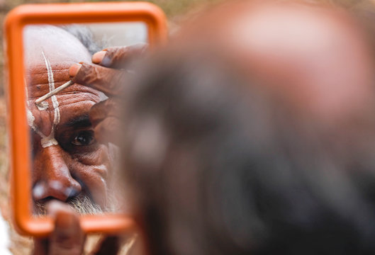 A Hindu holy man, or sadhu, looks into a mirror as he applies tika on his forehead at the premises of Pashupatinath Temple a day ahead of the Shivaratri festival in Kathmandu