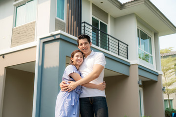 Portrait of Asian young couple standing and hugging together looking happy in front of their new house to start new life. Family, age, home, real estate and people concept..