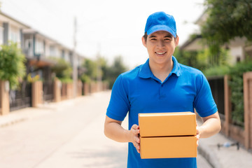Asian delivery young man in blue uniform smile and holding pile of cardboard boxes in front house village with copy space. Advertising, Business, Transportation Concept..