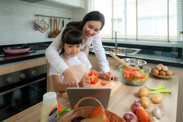 Portrait of beautiful Asian young woman and her daughter cooking salad for lunch using online internet in a digital tablet seach recipe while making food, Family life love relationship.