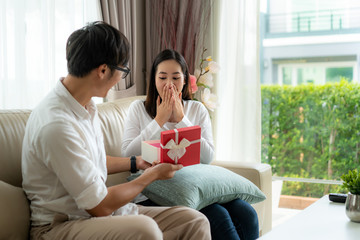 Asian man give a woman a red gift box. She look at the gift in the box and surprise at the wedding anniversary or her birthday in living room at house. Love, relationship, wedding.