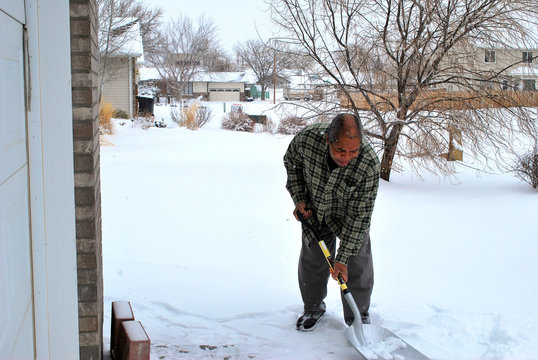 Man shoveling winter snow outside.