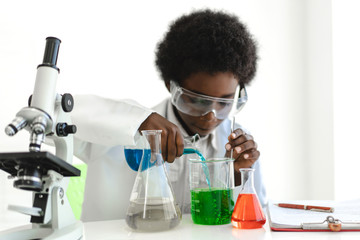 African american boy students learning and doing a chemical experiment and holding test tube in hands in science class on the table.Education concept