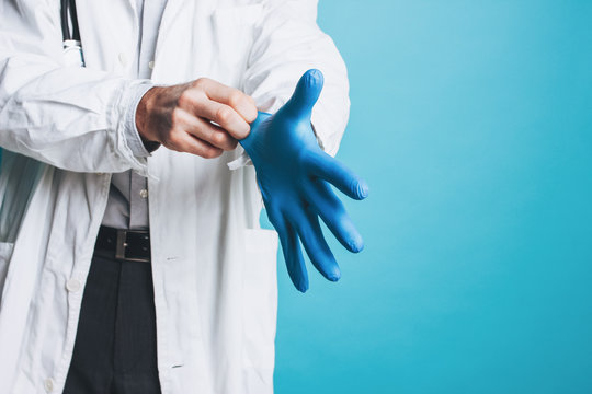 Crop photo of man doctor in white coat puts on rubber medical gloves  isolated on blue background