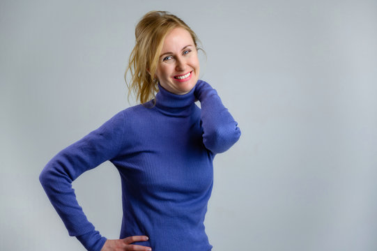 Portrait of a happy woman 35 years old blonde with a smile in a blue jacket on a blue background