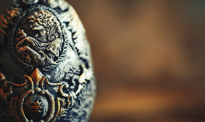 Close up photo vinage Easter egg decorated with papier-mache hand made, beautiful decorations on egg at stand, pictures on egg, look like stones eggs, jewellery, on wooden background.