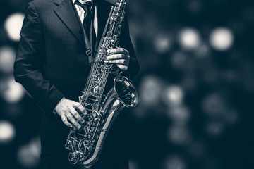 Saxophone player isolated at the left border of a black background