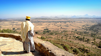 African Priest Watching the wide Desert of Ethiopia Unidentified Ethiopian Priest In traditional Clothing Looking on Wide Desert Mountains