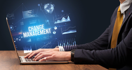 Businessman working on laptop with CHANGE MANAGEMENT inscription, new business concept
