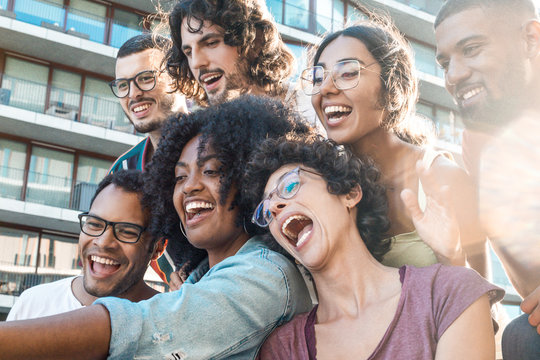 Funny mix raced friends taking group selfie outside. Multiethnic men and women posing, singing and laughing at phone camera. Funny selfie concept