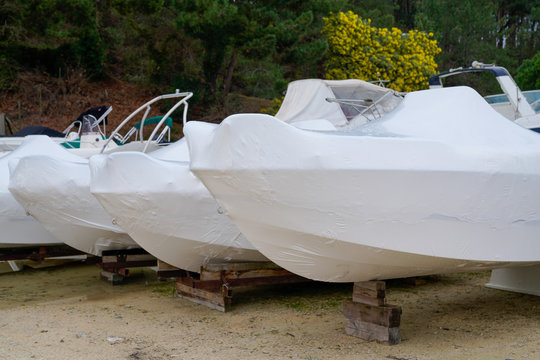 power boat parking covered white protective plastic film new modern boats in cover casing shrink wrap on sailboat stored for season cold winter