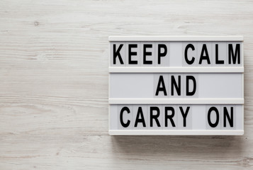 'Keep calm and carry on' words on a modern board on a white wooden surface, top view. Overhead, from above, flat lay. Copy space.