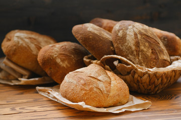 Assortment of baked bread on wooden table background. Bread background, top view of white, black and rye loaves. Healthy food.