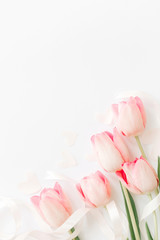 Pink tulips with ribbon and hearts on white background, flat lay. Stylish soft vertical image. Happy womens day. Greeting card mockup with space for text. Happy Mothers day. Valentines day