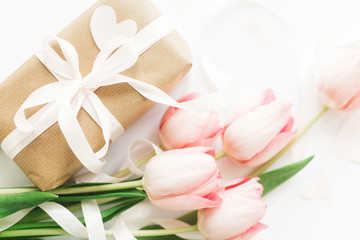 Pink tulips flat lay with ribbon and gift box on white background. Stylish soft image of spring flowers. Happy womens day. Greeting card mockup. Happy Mothers day. Hello spring