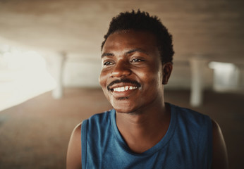 Happy portrait of a happy young african american young athlete looking away at outdoors Fotomurales