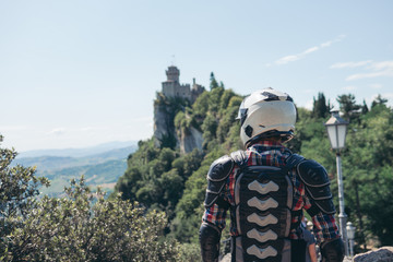 Back view. Man dressed in a motorcycle outfit and white helmet. body protection turtle. Fortress on top of the mountain background. Copy space. Motorbike travel. Pass of the witches San Marino Wall mural