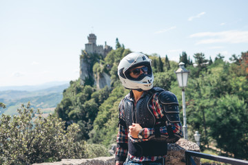 Man dressed in a motorcycle outfit and white helmet and sunglasses. body protection turtle. Fortress on background. Mountains. Stylish. copy space. Pass of the witches San Marino, Italy Wall mural