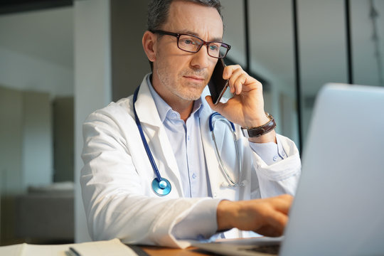 Doctor in office working on laptop talking on phone