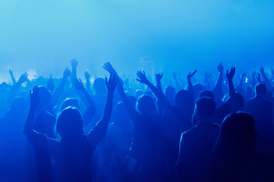 Silhouette of crowd raised hands on concert, music show.