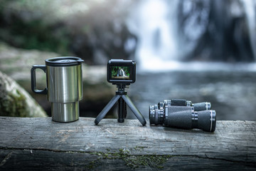 action camera,coffee cup,binoculars on wood with the waterfall behind.
