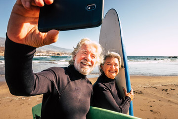 couple of pensioners seniors taking a selfie together at the beach with their wetsuits and surfboards - mature people learning surfing