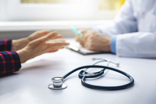 medical consultation - doctor talking to patient in clinic office. focus on stethoscope