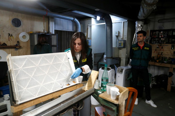 A Spanish civil guard shows cigarettes in an illegal underground tobacco factory during a police raid in Monda