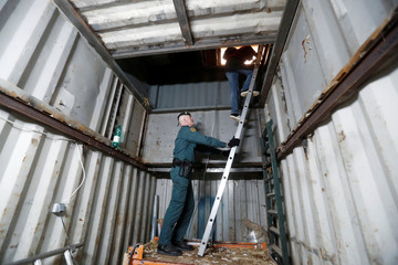 A Spanish civil guard helps a journalist to enter an illegal underground tobacco factory during a police raid in Monda