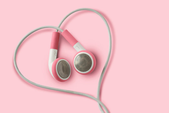 Pink earphones in heart shape on pink background - Concept of love, listening and support to women