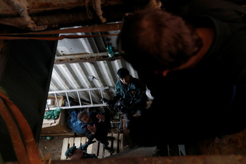 Spanish civil guard help journalists enter an illegal underground tobacco factory during a police raid in Monda