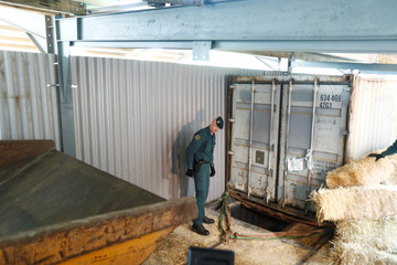 A Spanish civil guard stands at the entrance of an illegal underground tobacco factory during a police raid in Monda