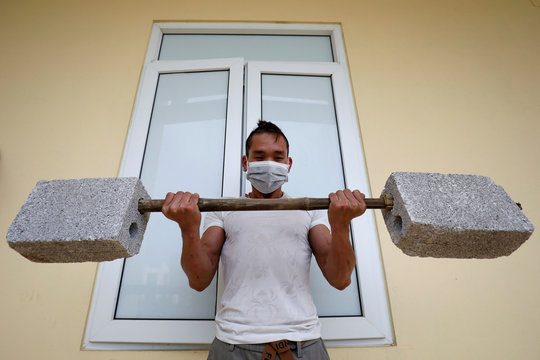 A Vietnamese man who come back from China, works out with a makeshift weights as he stays quarantined at a military base in Lang Son province, Vietnam