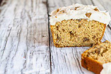 """Keto """"Carrot"""" Cake without the carrots to truly stay in ketosis for Easter. Loaf is baked with almond flour and walnuts and frosted with a sugar free cream cheese frosting. Blurred Background."""