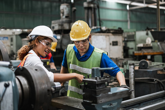 Man and woman engineer industry worker wearing hard hat in factory,