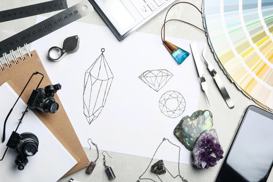 Flat lay composition with drawing of jewelry on light grey table. Designer's workplace