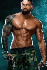 Athlete bodybuilder on black background with lights and smoke. Men fashion. Portrait of a brutal bearded man topless with chains.
