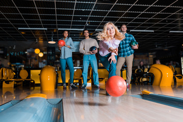 smiling blonde girl throwing bowling ball on skittle alley near multicultural friends
