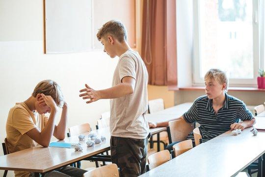Mean boys bullying a classmate sitting at school desk