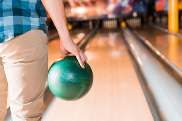 partial view of young man holding bowling ball near skittle alley