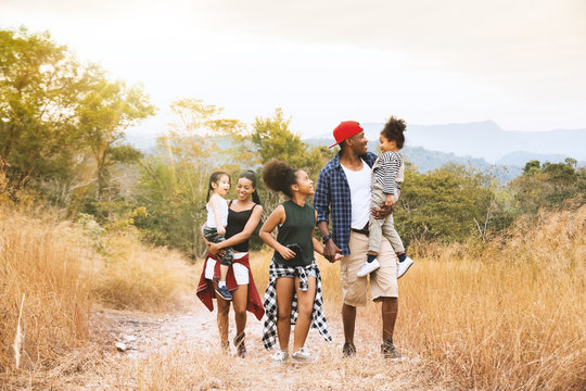 Happy mixed race big family with father, mother and child daughter walking on country road. Travel vacation concept