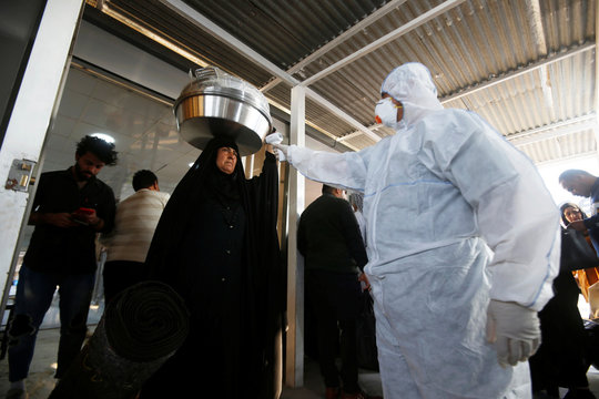 An Iraqi medical staff member checks a passenger's temperature, amid the new coronavirus outbreak, upon her arrival to Shalamcha Border Crossing