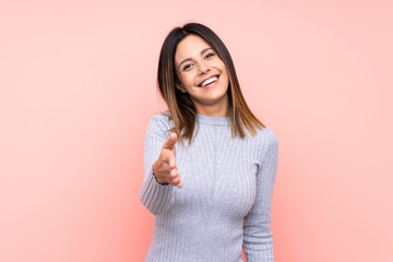 Woman over isolated pink background shaking hands for closing a good deal