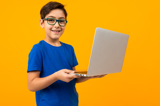 boy in blue t-shirt is typing on laptop on yellow studio background