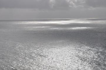 Fototapeta bezkresne morze w słońcu za chmurami obraz