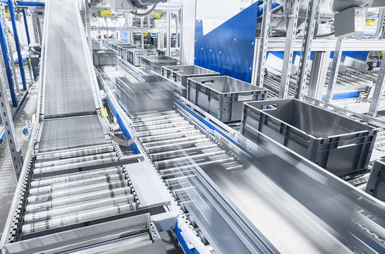 Modern conveyor system with boxes in motion, shallow depth of field.