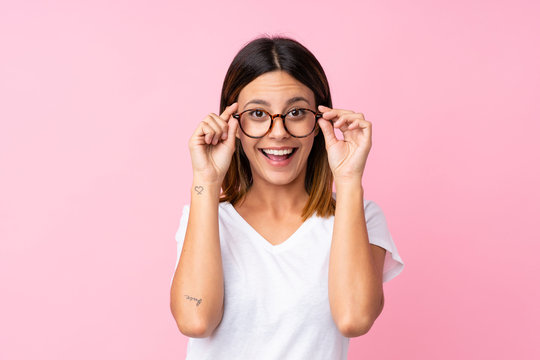 Young woman over isolated pink background with glasses and surprised
