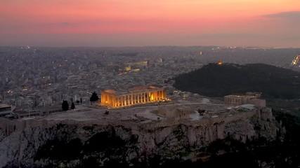 Fototapete - Der beleuchtete Parthenon Tempel auf der Akropolis in Athen, Griechenland, umgeben von der Altstadt bis hin zum Meer bei Sonnenuntergang